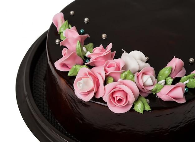 Decoraciones oscuras de la torta de chocolate del primer con las frutas coloridas de la formación de hielo en el fondo blanco Foto Premium