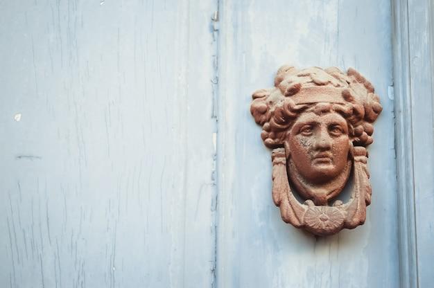 Decorado perilla de la puerta cara de metal en una puerta de madera azul Foto gratis