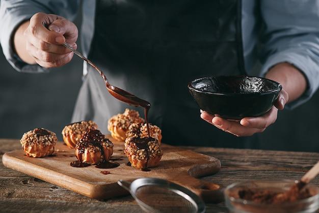 Decorando deliciosos canutillos caseros con chocolate y maní Foto gratis