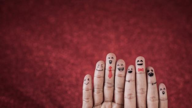 Dedo con emoción sobre fondo rojo Foto gratis