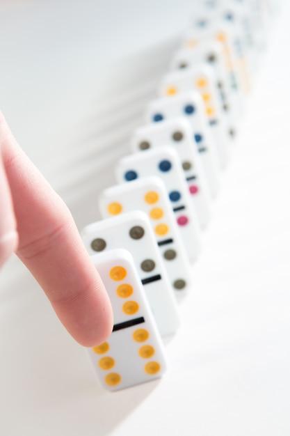 Dedo a punto de derribar la línea de dominós   Descargar Fotos premium