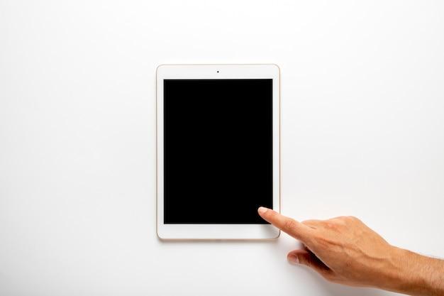 Dedo tocando la pantalla de la tableta plana Foto gratis