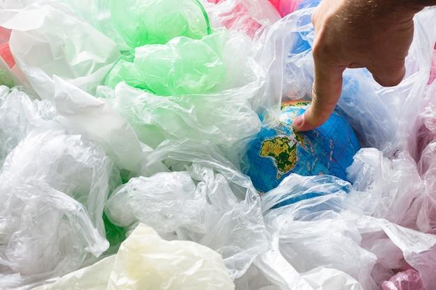 Dedo tocando la tierra rodeada de bolsas de plástico Foto Premium
