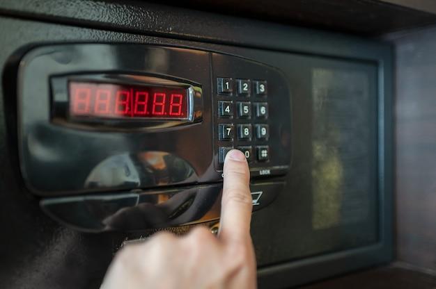 Los dedos presionan las teclas numéricas de la caja fuerte eléctrica. Foto Premium