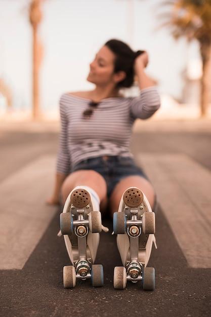Defocused joven mujer patinadora sentada en el camino con patines en sus piernas Foto gratis