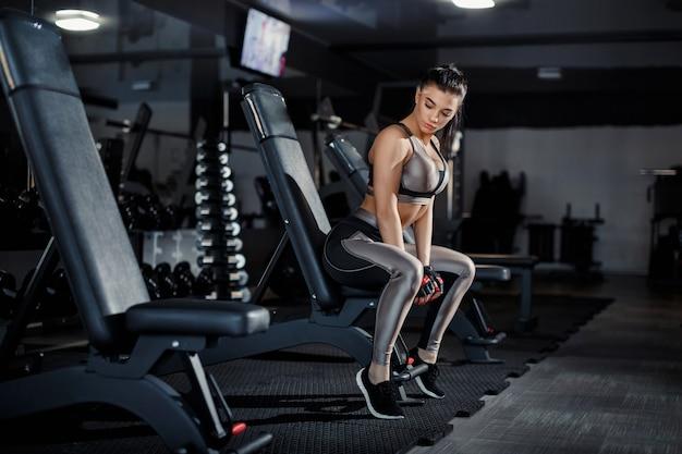 Delgado, fisicoculturista, levanta pesas pesadas de pie frente al espejo mientras entrena en el gimnasio. concepto deportivo, quemagrasas y un estilo de vida saludable. Foto Premium