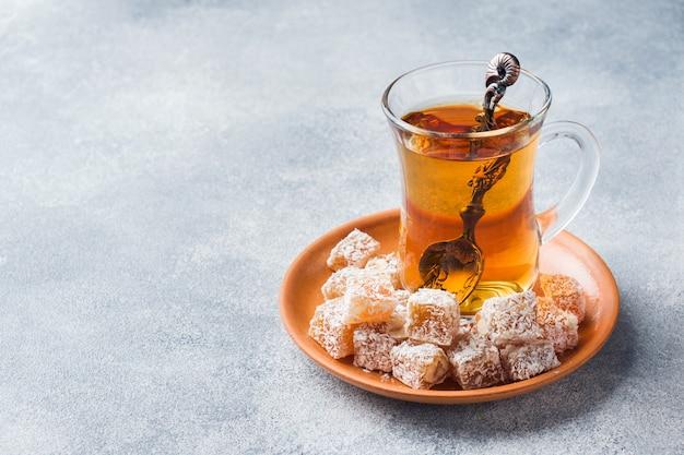 Delicias turcas con avellana en un recipiente de metal tallado y té en una taza de vidrio Foto Premium