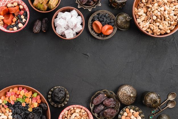 Delicias turcas con frutos secos; nueces; lukum y baklava sobre fondo negro de concreto Foto gratis
