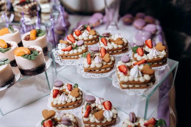 Deliciosa barra de caramelo con postres de mousse y galletas en forma de corazones Foto gratis