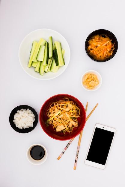Deliciosa comida asiática con ensalada; salsas y teléfono inteligente sobre fondo blanco Foto gratis