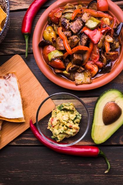 Deliciosa pita junto a la comida entre verduras. Foto gratis