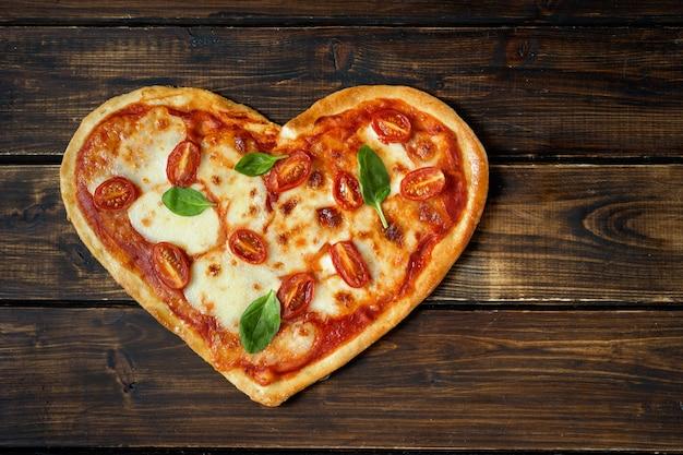 Deliciosa pizza italiana en forma de corazón en madera Foto Premium