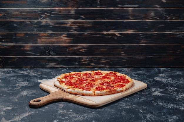 Deliciosa pizza napolitana en un tablero Foto gratis