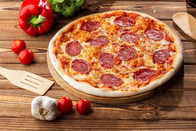 Deliciosa pizza de pepperoni casera caliente en la mesa de madera. pizza de pepperoni - pizza casera fresca con salsa de pepperoni, queso y tomate sobre fondo de piedra negra rústica con espacio de copia. Foto Premium