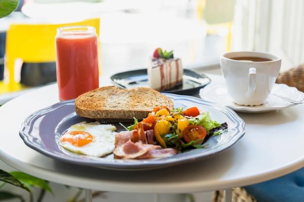 Deliciosa rebanada de pastel; desayuno; taza de café y batido servido en la mesa Foto gratis