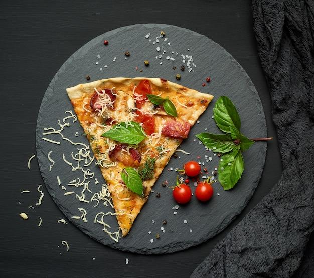 Deliciosa rebanada de pizza triangular con salchichas ahumadas, champiñones, tomates, queso y hojas de albahaca Foto Premium