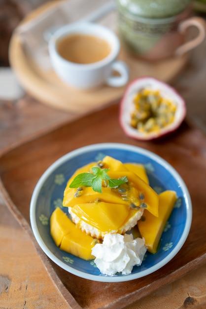 Deliciosa tarta de queso con maracuyá y mango en mesa de madera. Foto Premium