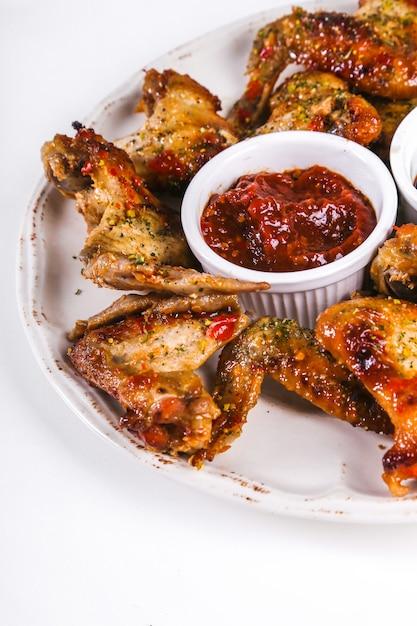 Deliciosas alitas de pollo en la mesa de madera Foto gratis