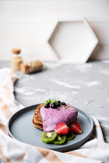 Deliciosas crepes con mitades de fresa y kiwi alta vista Foto gratis