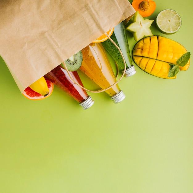 Deliciosas frutas y jugos en bolsa de papel copyspace. Foto gratis