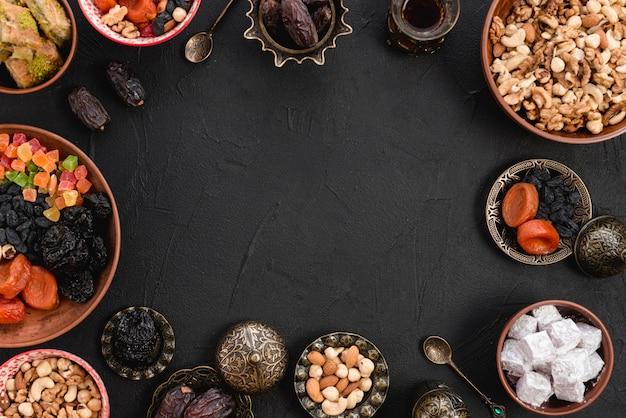 Deliciosas frutas secas árabes; nueces; lukum; baklava sobre fondo negro Foto gratis