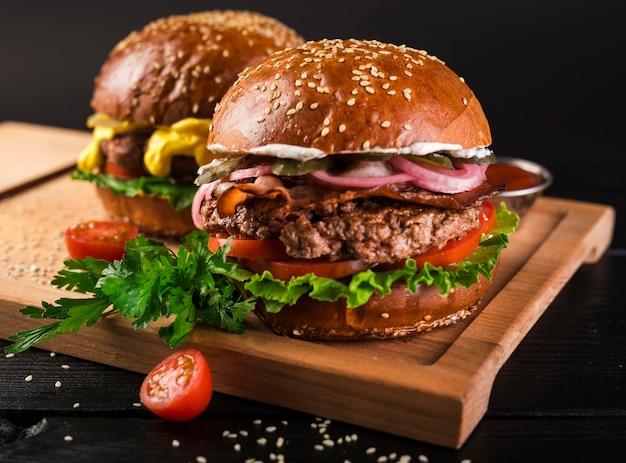 Deliciosas hamburguesas de carne sobre una tabla de madera Foto gratis