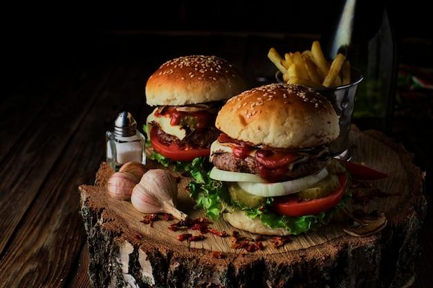 Deliciosas hamburguesas en un estilo rústico sobre fondo de madera oscura. Foto Premium