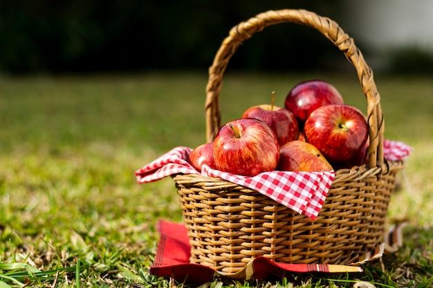 Deliciosas manzanas rojas en cesta de paja Foto gratis