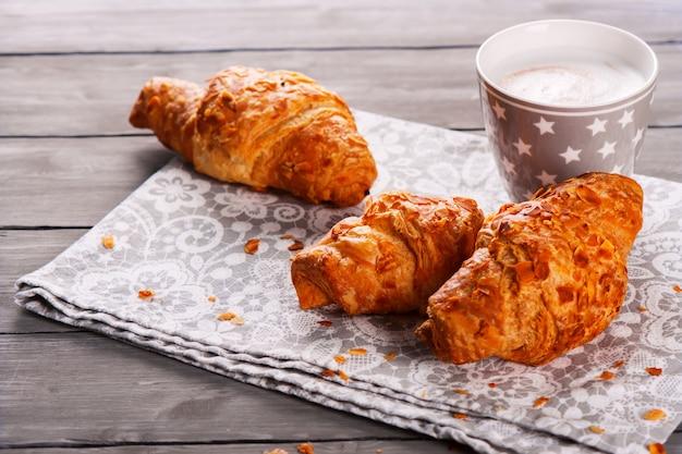 Delicioso desayuno con croissants frescos y una taza de capuchino sobre fondo de madera gris Foto Premium