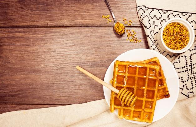 Delicioso gofre belga con miel y polen de abeja en escritorio de madera Foto gratis