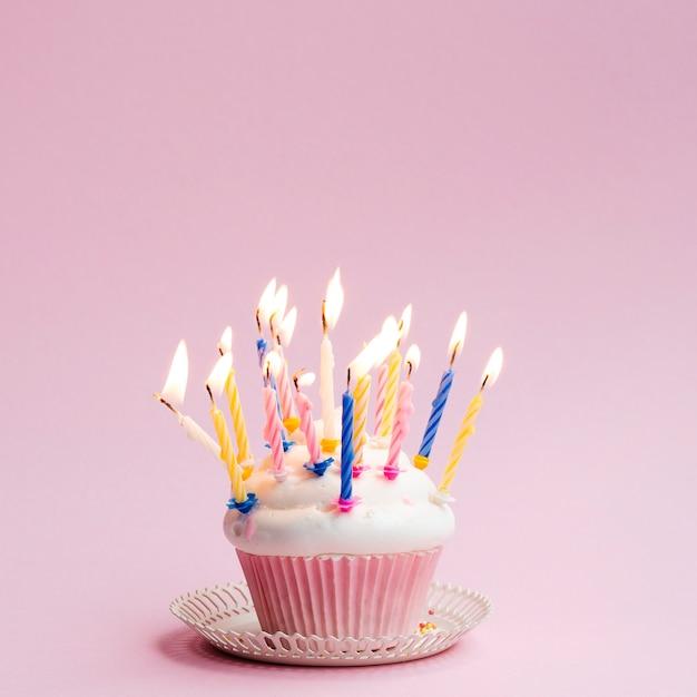 Delicioso muffin de cumpleaños con velas de colores Foto gratis
