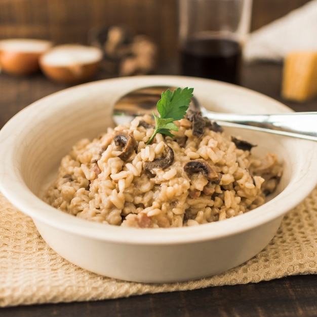Delicioso risotto de setas en un tazón blanco con cuchara Foto gratis