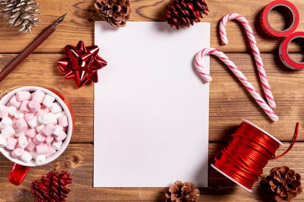 Deliciosos bastones de navidad y hoja en blanco Foto gratis