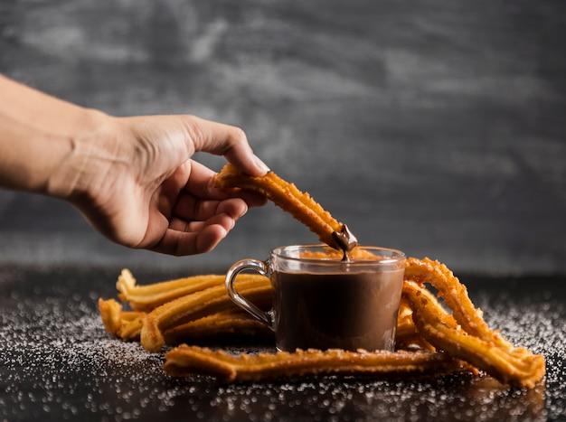 Deliciosos churros con chocolate derretido en la mesa Foto gratis
