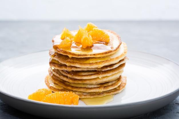 Deliciosos panqueques caseros con mandarinas y miel en un plato sobre la mesa. Foto Premium