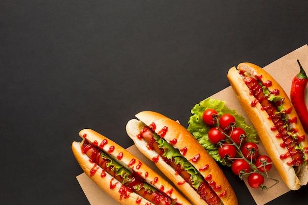 Deliciosos perritos calientes y tomates. Foto gratis