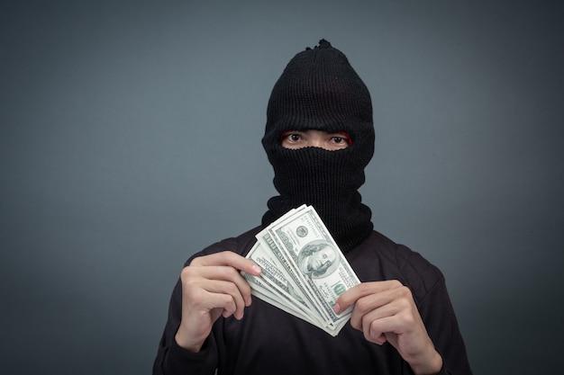 Los delincuentes negros llevan un hilo en la cabeza, sostienen una tarjeta de dólar en gris Foto gratis