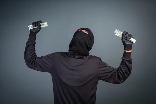 Los delincuentes usan máscaras negras para sostener las tarjetas de dólar en gris Foto gratis