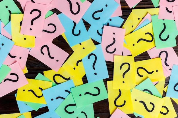 Demasiadas preguntas sobre fondo de madera. pila de notas de papel de colores con signos de interrogación. vista superior Foto Premium