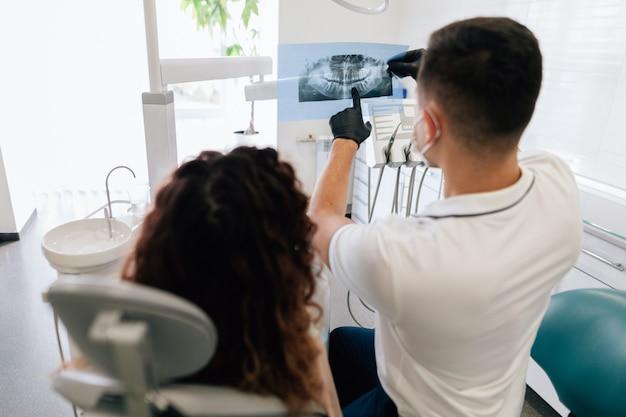 Dentista apuntando a la radiografía con el paciente Foto gratis