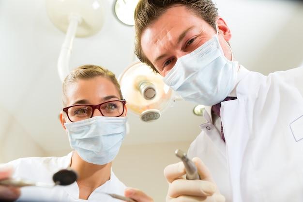 Dentista y asistente en un tratamiento, desde la perspectiva de un paciente. Foto Premium