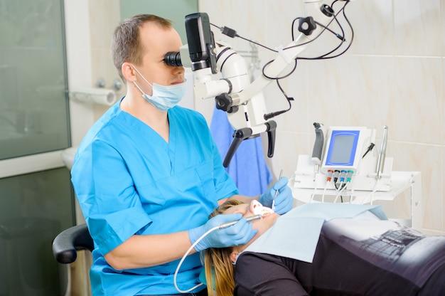 Dentista masculino trabajando con microscopio en la clínica dentista moderna Foto Premium