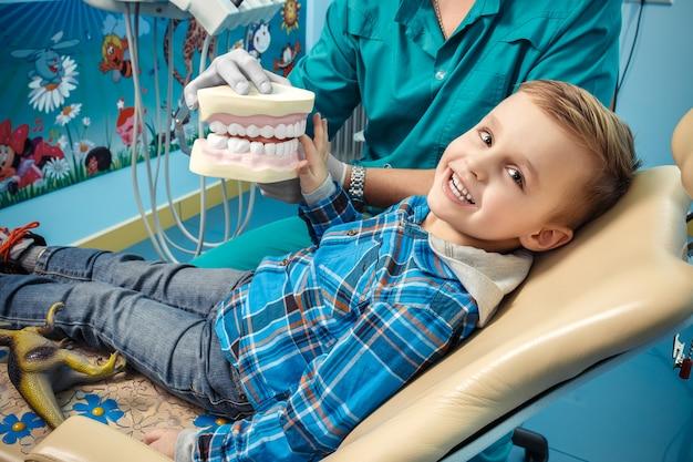 Dentista muestra una dentadura al niño Foto Premium