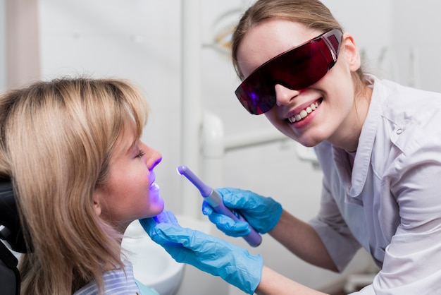 Dentista realizando blanqueamiento dental Foto gratis