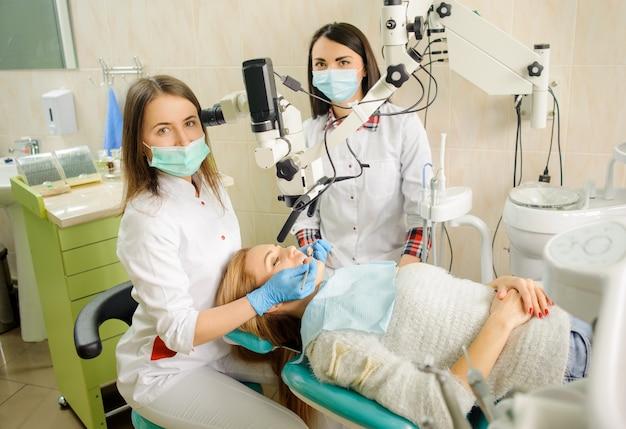 Dentista de sexo femenino que trata la caries usando el microscopio en la oficina del dentista Foto Premium