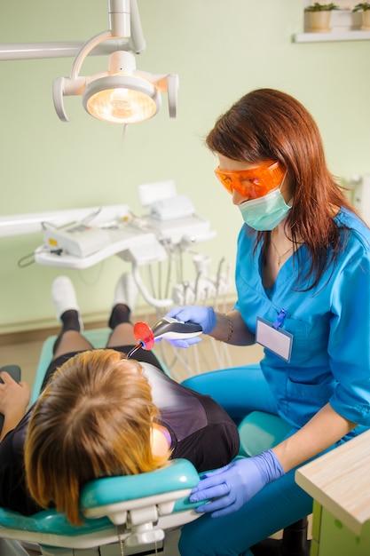El dentista está sosteniendo una lámpara de fotopolímero de dentista que trata al paciente en la clínica Foto Premium