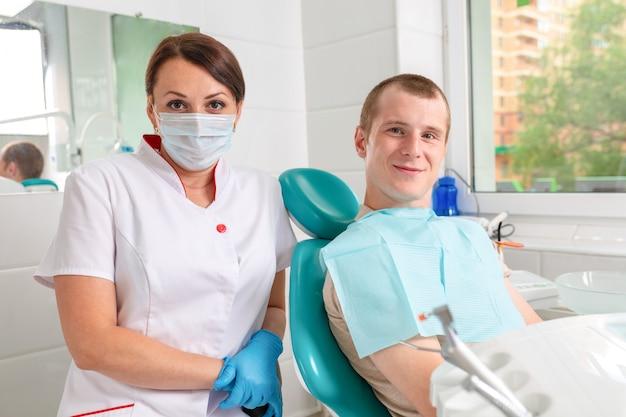La dentista y su paciente feliz miran a la cámara y sonríen Foto Premium