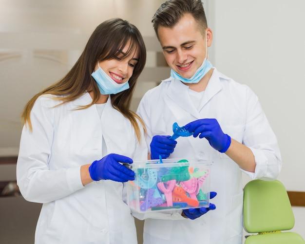 Dentistas sonriendo y sosteniendo la caja de retenedores Foto gratis