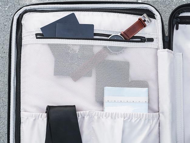 Dentro de la maleta se sientan los pasaportes y un reloj Foto gratis