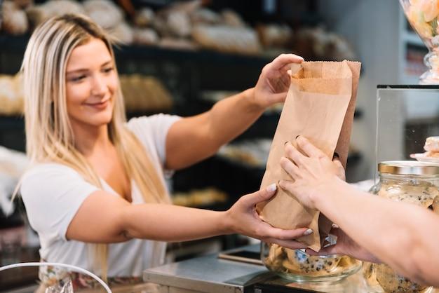 Dependienta dando bolsa de croisants Foto gratis